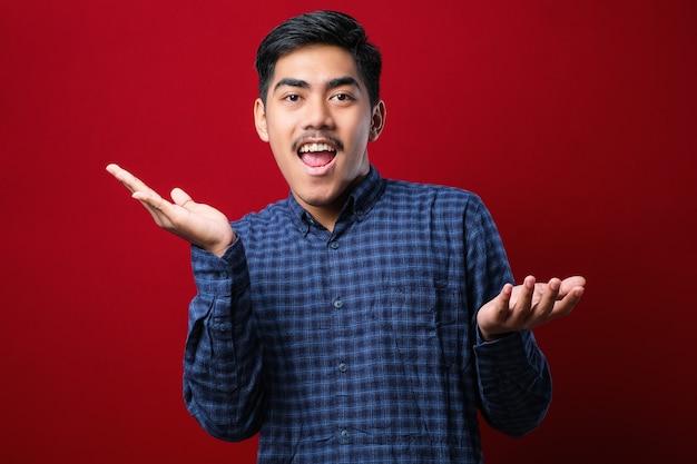 赤い背景の上に立っているカジュアルなシャツを着て陽気なハンサムな若いハンサムな男