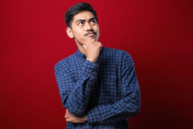 빨간 배경 위에 캐주얼 셔츠를 입은 젊고 잘생긴 남자는 질문에 대해 걱정하고 턱에 손을 대고 걱정하고 긴장합니다