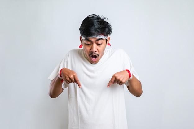 白い背景の上に立っているカジュアルなシャツを着ている若いハンサムな男広告、驚いた顔と開いた口を示す指で下向き