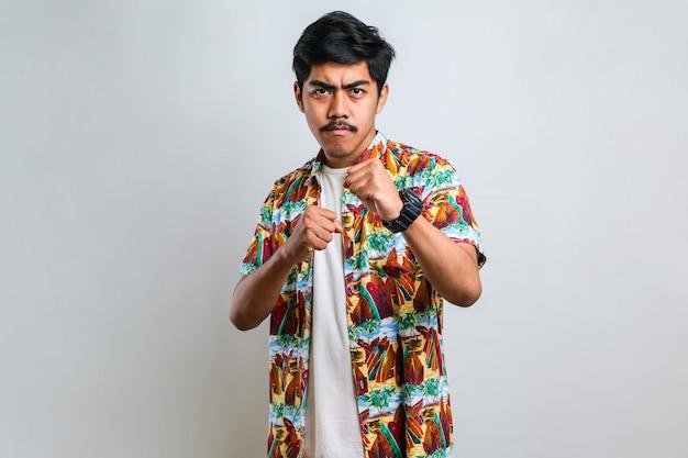 白い背景の上に立っているカジュアルなシャツを着ている若いハンサムな男は、戦うために拳をパンチ、攻撃的で怒っている攻撃、脅威と暴力