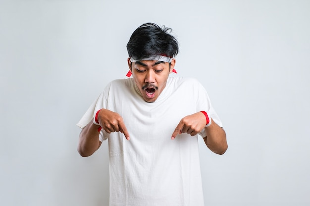Young handsome man wearing casual shirt standing over white background pointing down with fingers showing advertisement, surprised face and open mouth