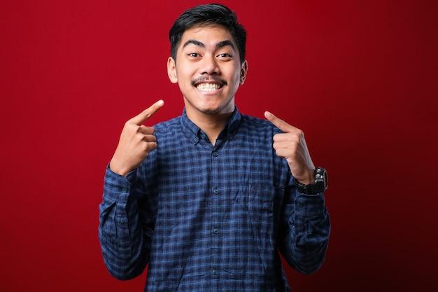 Молодой красивый мужчина в повседневном свитере, стоящий на изолированном красном фоне, улыбаясь, веселый показ и указывая пальцами, зубами и ртом. концепция стоматологического здоровья.