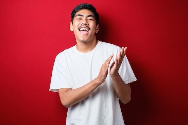 赤い背景の上にカジュアルなtシャツを着て、幸せで楽しい拍手と拍手、誇らしげな手を一緒に笑って若いハンサムな男