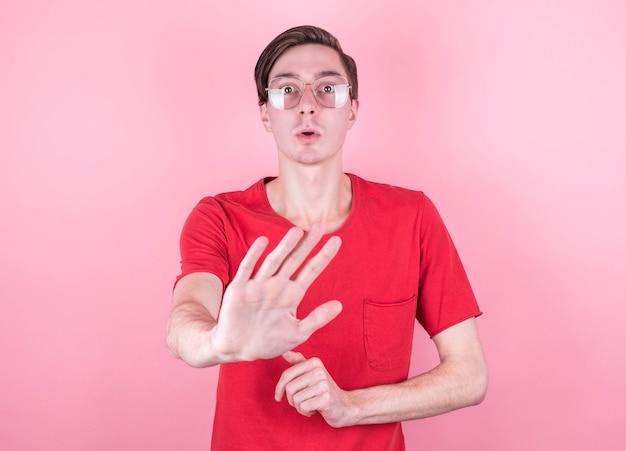 Молодой красавец в повседневной футболке стоит над розовой стеной и перестает петь ладонью. предупреждающее выражение с негативным и серьезным жестом на лице.