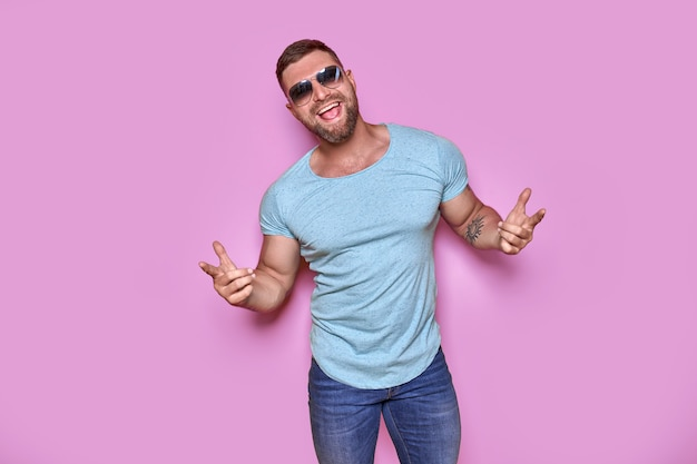 캐주얼 티셔츠를 입은 젊고 잘생긴 남자가 손가락으로 가리키는 고립된 분홍색 배경 위에 서 있습니다...