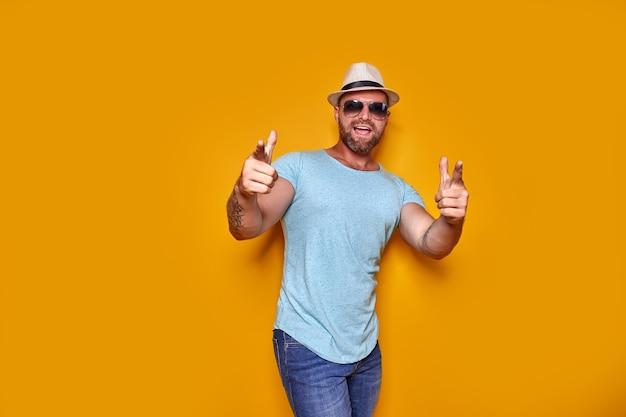 캐주얼 티셔츠를 입은 젊고 잘생긴 남자가 손가락으로 가리키는 고립된 노란색 배경 위에 서 있습니다...