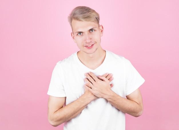 笑顔の孤立したピンクの背景にカジュアルな白いシャツを着て若いハンサムな男