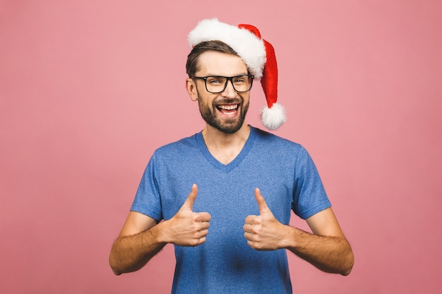 긍정적 인 미소 크리스마스 모자를 쓰고 젊은 잘 생긴 남자. 성공적인 표현. 엄지 손가락.