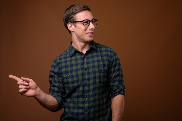 Young handsome man wearing eyeglasses on brown wall