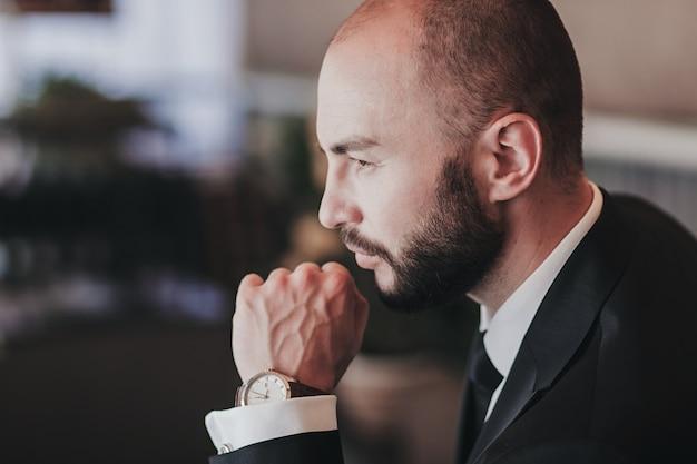 ファッション時計を身に着けている若いハンサムな男。肖像画の実業家