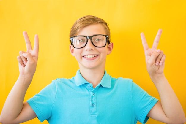 勝利のサインをしている指を示すカメラを見て笑みを浮かべて孤立した背景に眼鏡をかけている若いハンサムな男。二番