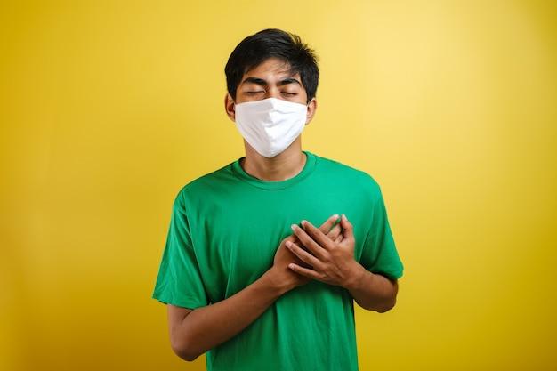 Молодой красавец в зеленой футболке и хирургической маске, стоящий на изолированном фоне, улыбаясь руками на груди с закрытыми глазами и благодарным жестом на лице. концепция здоровья.