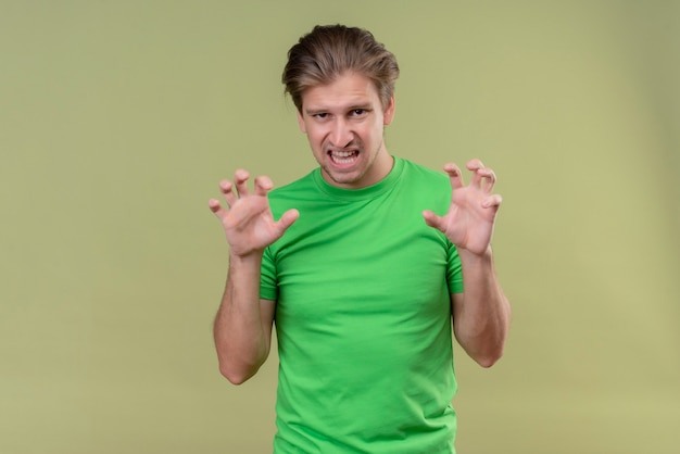 Giovane uomo bello che indossa la maglietta verde ringhiando come un animale che fa gesto di artigli di gatto in piedi sopra la parete verde