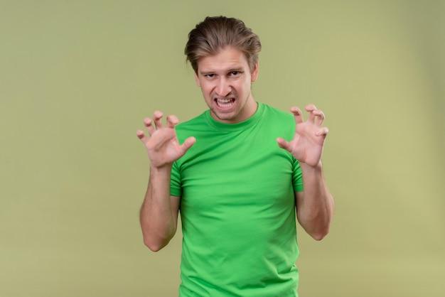 Молодой красавец в зеленой футболке рычащий, как животное, делающее жест кошачьих когтей, стоящий над зеленой стеной