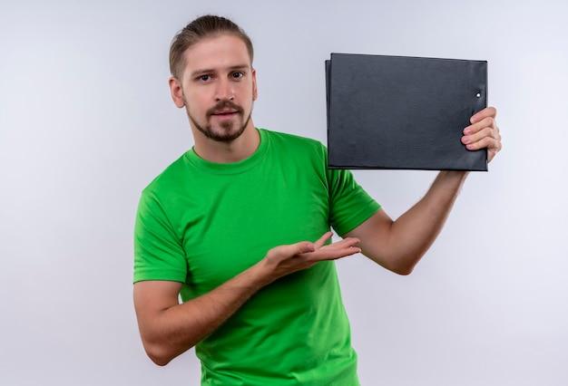 白い背景の上に自信を持って立っているを探している彼の手の腕でそれを提示するドキュメントケースを保持している緑のtシャツを着ている若いハンサムな男