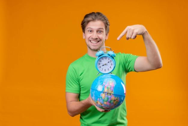 Giovane uomo bello che indossa la maglietta verde che tiene il globo e la sveglia che indica con il dito sorridendo allegramente in piedi sopra la parete arancione