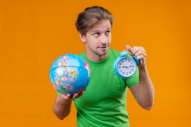 Giovane uomo bello che indossa la maglietta verde che tiene il globo e la sveglia che sorride astutamente che osserva da parte in piedi sopra il muro arancione