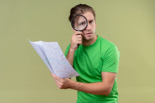 Young handsome man wearing green t-shirt holding map looking through magnifying glass at camera with serious expression on face standing over green wall