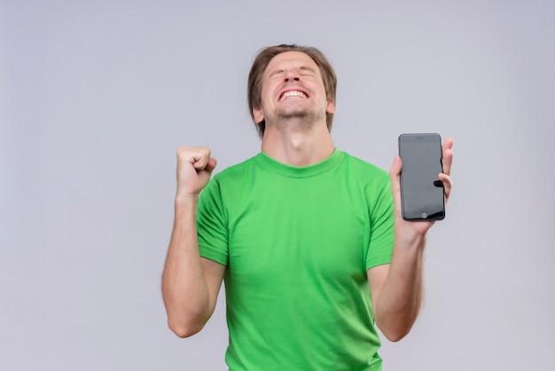 白い壁の上に立って彼の成功を喜んで携帯電話狂気の幸せな握りこぶしを保持している緑のtシャツを着ている若いハンサムな男