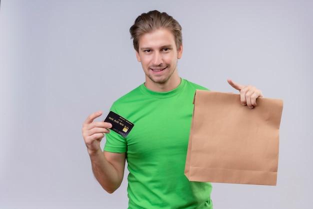 紙のパッケージとクレジットカードを保持している緑のtシャツを着ている若いハンサムな男