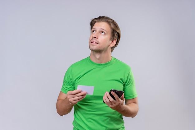 スマートフォンとクレジットカードを保持している緑のtシャツを着ている若いハンサムな男が白い壁に立って選択をしようと考えて顔の物思いに沈んだ表情で見上げる