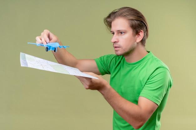 緑の壁の上に立っている顔に真剣な表情でおもちゃの飛行機と地図を保持している緑のtシャツを着ている若いハンサムな男