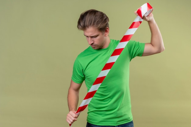 Young handsome man wearing green t-shirt holding and using adhesive tape looking with serious expression on face standing over green wall