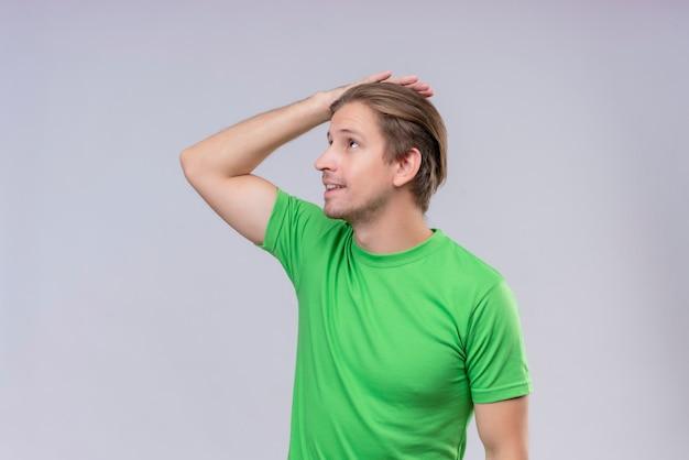 よそ見緑のtシャツを着ている若いハンサムな男