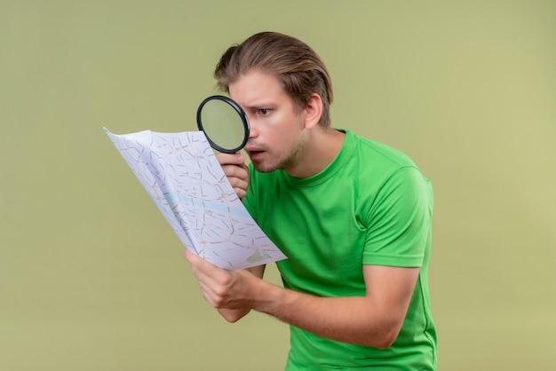 虫眼鏡を通して地図を見て緑のtシャツを着ている若いハンサムな男驚いて緑の壁の上に立って