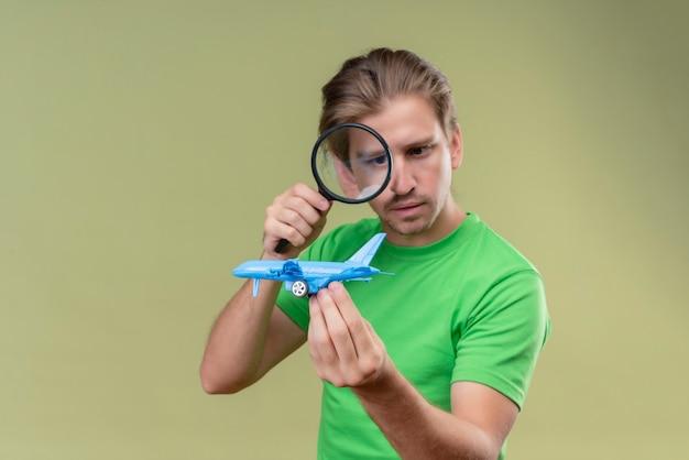緑の壁の上に立っている顔に真剣な表情で虫眼鏡を通しておもちゃの飛行機を見て緑のtシャツを着ている若いハンサムな男