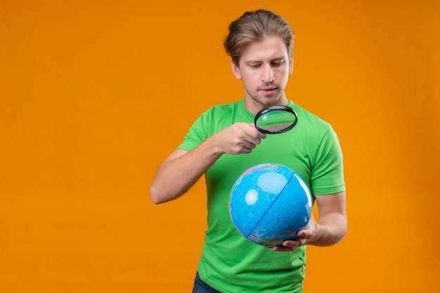 Young handsome man wearing green t-shirt looking at globe through magnifying glass with serious face standing over orange wall