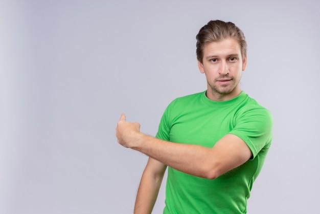探している、笑みを浮かべて、後ろに何かを指している緑のtシャツを着ている若いハンサムな男