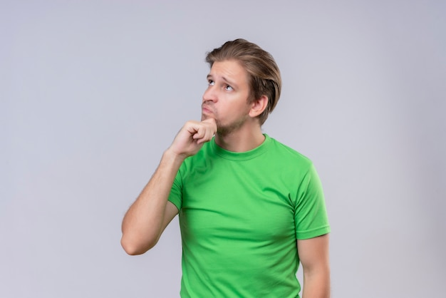 Young handsome man wearing green t-shirt looking up with hand on chin with pensive expression on face standing over white wall 2