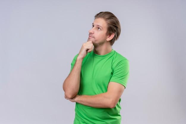 白い壁に立っている顔に物思いに沈んだ表情であごに手で見上げる緑のtシャツを着ている若いハンサムな男