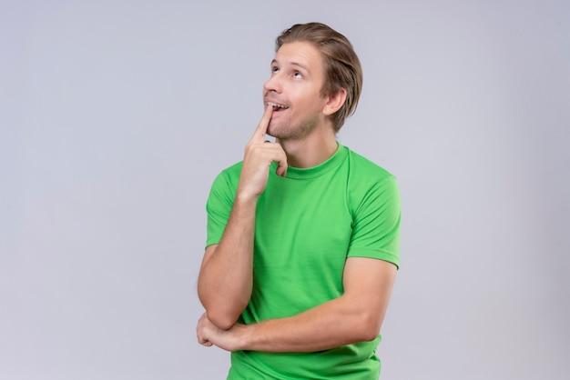 白い壁を越えて肯定的な立っていると物思いに沈んだ表情を考えて見上げる緑のtシャツを着ている若いハンサムな男