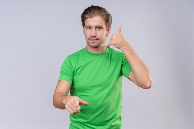 緑のtシャツを着ている若いハンサムな男は白い壁に優しい立っている笑顔ジェスチャーを呼び出す