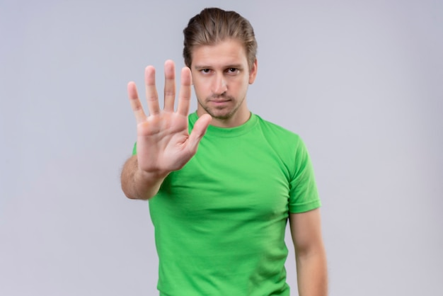 Young handsome man wearing green t-shirt making stop sign with open hand