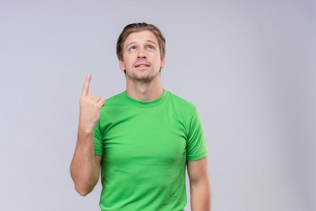 緑のtシャツの人差し指を身に着けている若いハンサムな男