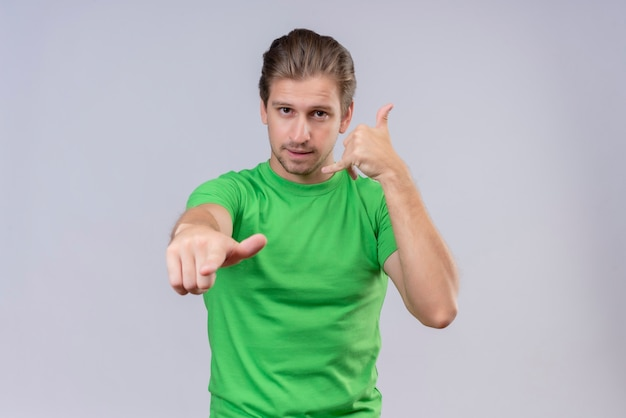 Молодой красавец в зеленой футболке указывает вперед и делает жест звонка