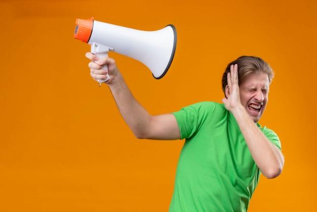 オレンジ色の壁の上に立ってイライラ立って目を閉じてメガホンに対して手で保護する緑のtシャツを着ている若いハンサムな男