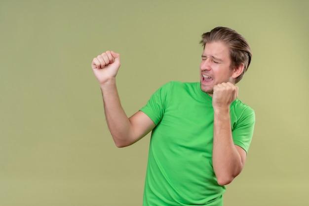 Молодой красавец в зеленой футболке готов драться жестом защиты кулаком с расстроенным лицом, стоящим над зеленой стеной