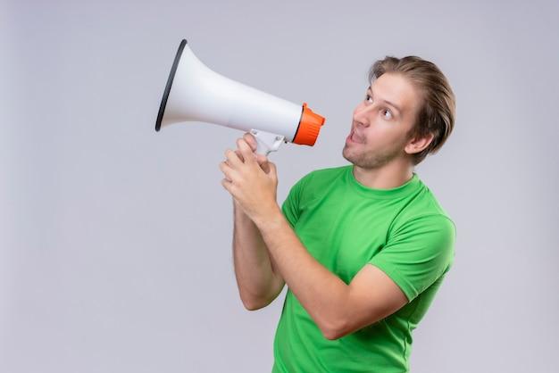 Giovane uomo bello che indossa la maglietta verde che grida al megafono