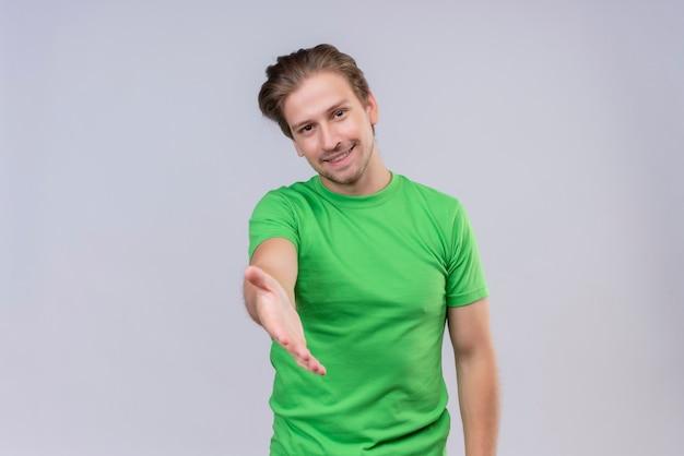 緑のtシャツを着ている若いハンサムな男笑顔白い壁の上に立っている手を提供しているフレンドリーな挨拶ジェスチャー