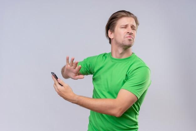 Молодой красавец в зеленой футболке стоит над белой стеной