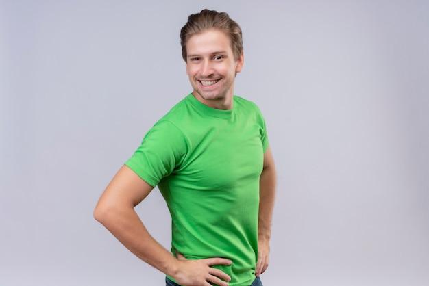 白い壁2に自信を持って自信を持って横に立っている緑のtシャツを着ている若いハンサムな男