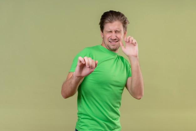 緑の壁の上に立って手を握って防衛ジェスチャーを作る目を閉じて立っている緑のtシャツを着ている若いハンサムな男
