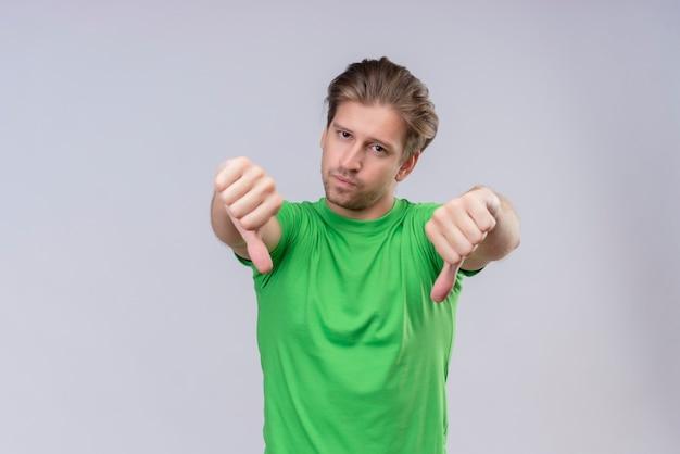 Молодой красавец в зеленой футболке несчастный показывает палец вниз, стоя над белой стеной