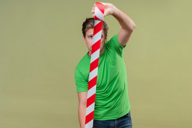 Young handsome man wearing green t-shirt using adhesive tape in looking confident standing over green wall