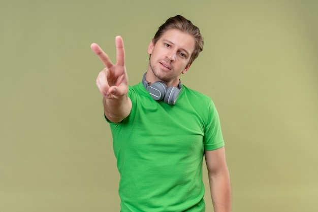 Young handsome man wearing green t-shirt with headphones smiling showing and pointing with fingers number two or victory sign standing over green wall