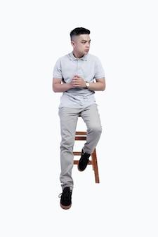 Молодой красавец в серой рубашке поло верескового цвета позирует в кресле